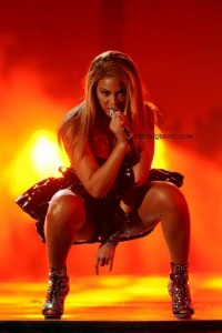 Beyonce, in one of her performances, shows the devil's horn hand signal (right hand), bottom.