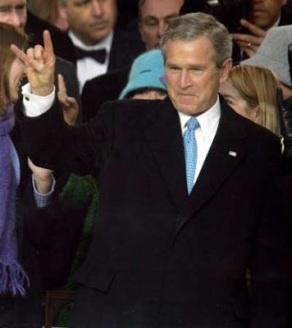 President George Bush flashing the devil's horn hand signal.